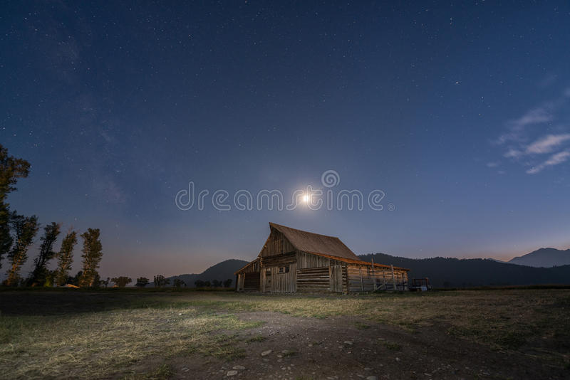 Måne och Vintergatan över den Moulton ladugården arkivbild