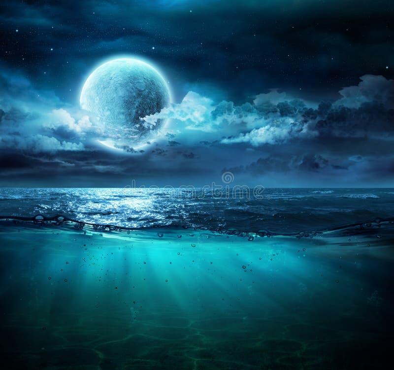 Måne på havet i magisk natt arkivfoto
