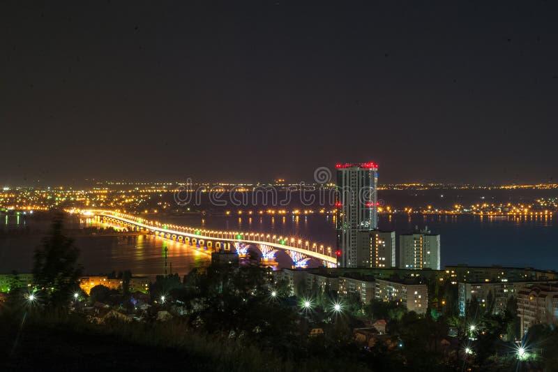 Måneförmörkelse Sikt av nattstaden av Saratov, Ryssland Ljusen av en metropolis i natten Sikt av bron över Volgen royaltyfria foton
