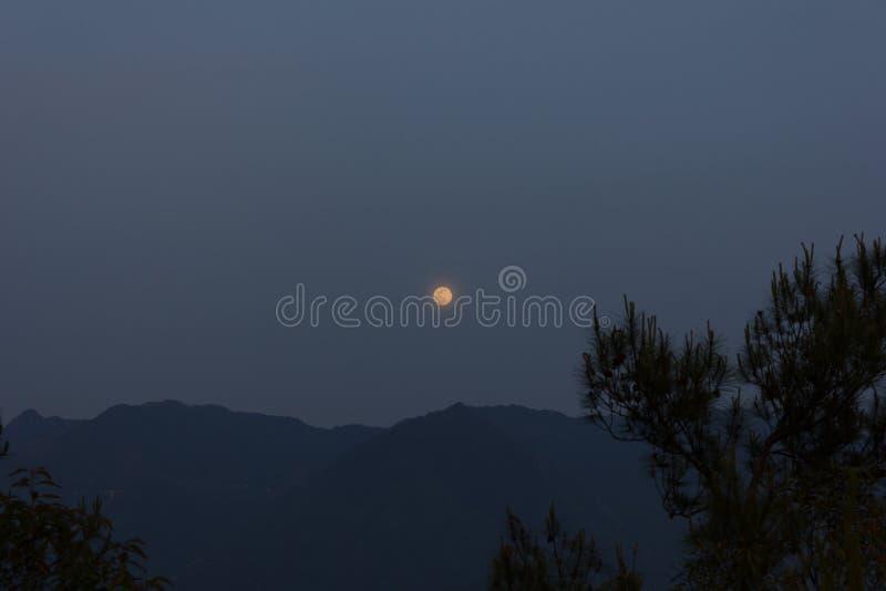 Månelöneförhöjning över ett berg arkivfoto