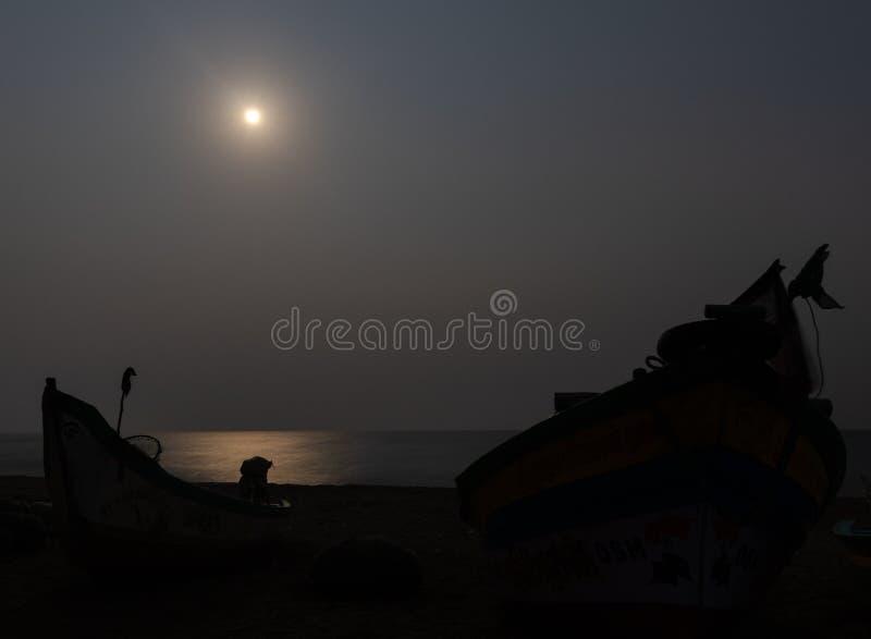 Måneljus på kusten med fiskarefartygskugga arkivbild
