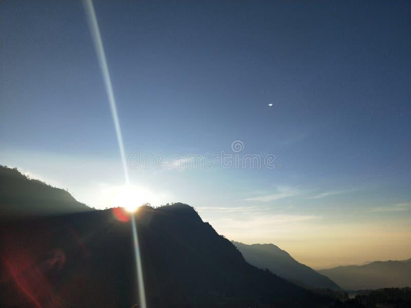 Månen kan ses fortfarande, när solen stiger arkivfoton