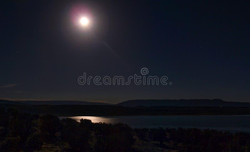 Månen reflekterar av Abiquiu sjön under natthimmel royaltyfria foton