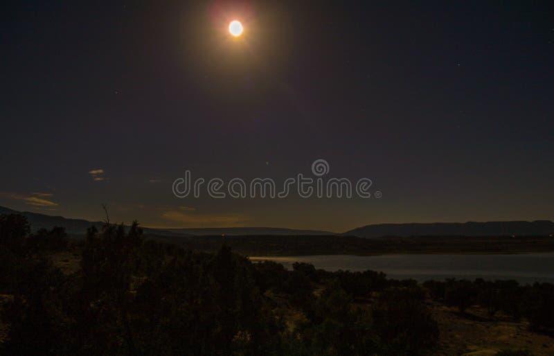 Månen reflekterar av Abiquiu sjön under natthimmel royaltyfri foto