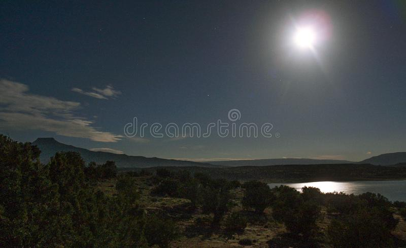 Månen reflekterar av Abiquiu sjön under natthimmel royaltyfri bild