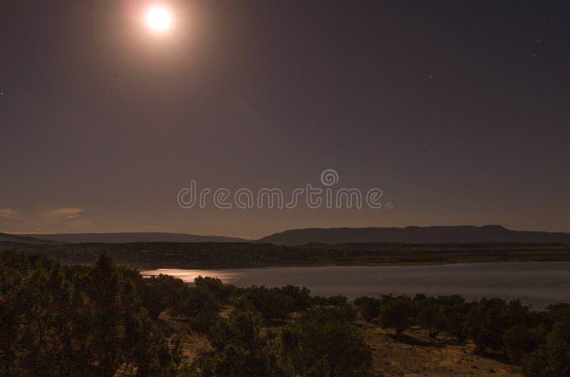 Månen reflekterar av Abiquiu sjön under natthimmel arkivbilder