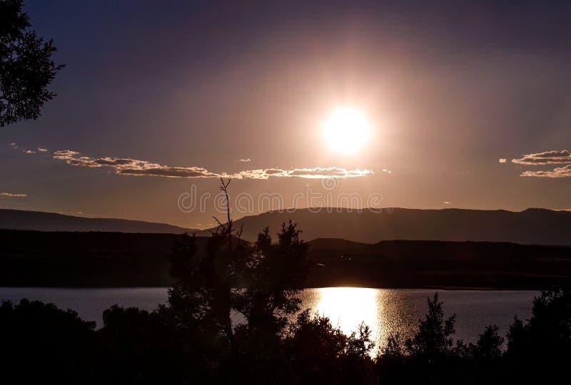 Månen reflekterar av Abiquiu sjön under natthimmel fotografering för bildbyråer