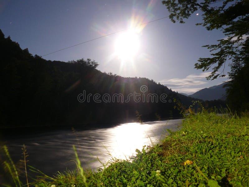 Månen vid natt på bakgrunden av floden fotografering för bildbyråer