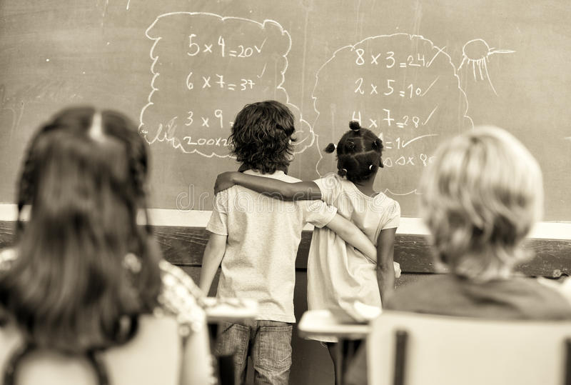 Mång- etniska elementära studenter omfamnade att lära matematik på krita royaltyfria foton