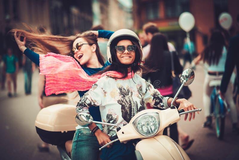 Mång- etniska flickor på en sparkcykel i europeisk stad royaltyfria foton