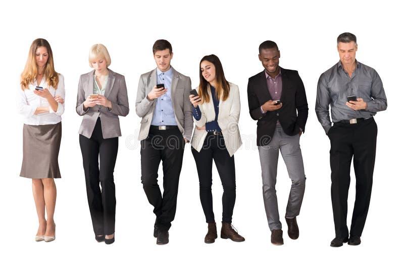 Mång- etniskt affärsfolk som använder mobiltelefoner arkivbild