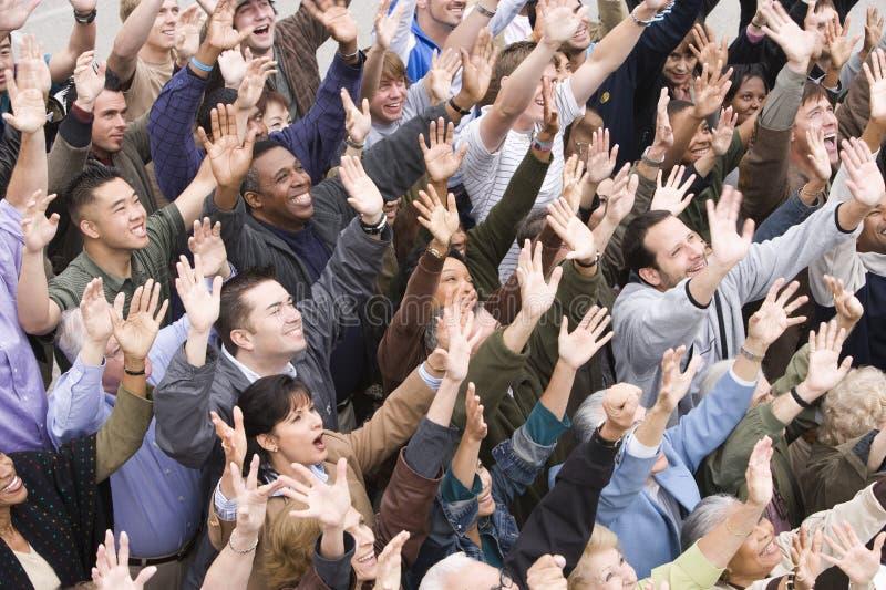 Mång- etniskt folk som tillsammans lyfter händer royaltyfri bild