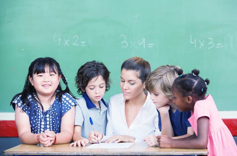 Mång- etniskt klassrum med förklarande matematiklesso för lärare arkivbild