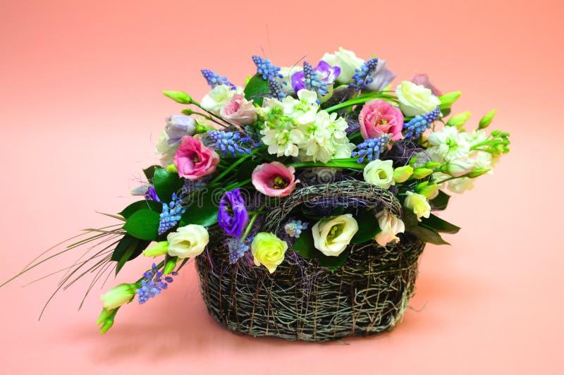 Mång--färgad bukett av blommor i korg royaltyfri bild