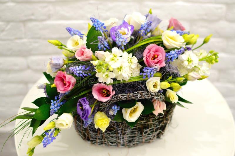 Mång--färgad bukett av blommor i korg arkivfoton