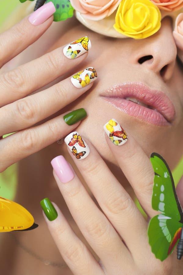 Mång--färgad manikyr på spikar med en design av fjärilar royaltyfria bilder