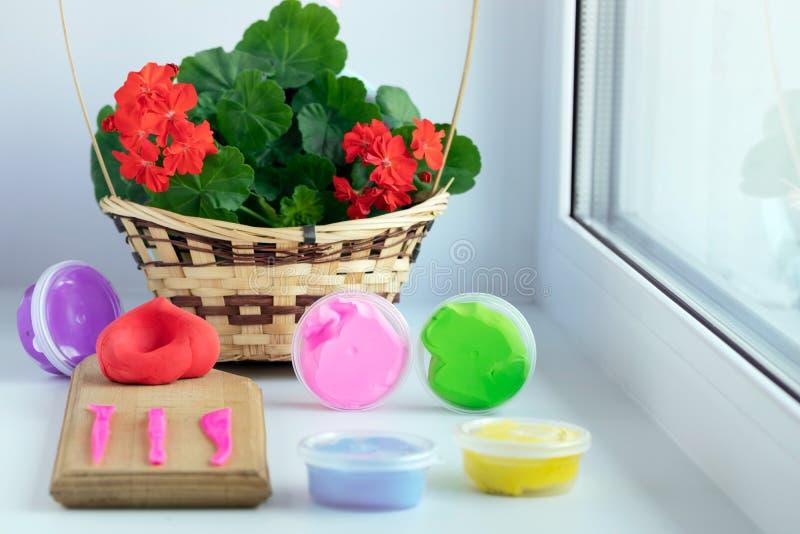 Mång--färgad plasticine för att modellera i en rund packe och hjälpmedel på ett träbräde förbereds för arbete Röd blomma i fotografering för bildbyråer