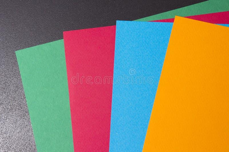 Mång--färgade ark av papper på en svart bakgrund Ark av papper av olika färger kulöra ark är fördelade ut i en fan arkivfoton