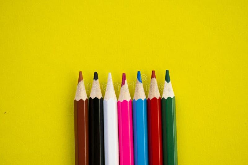 Mång--färgade blyertspennor på en gul bakgrund arkivfoton