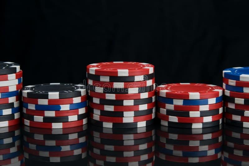 Mång--färgade chiper, för att spela i en kasino, ställning vid talrika pyramider, på en svart reflekterande tabell, finns det en  royaltyfria bilder