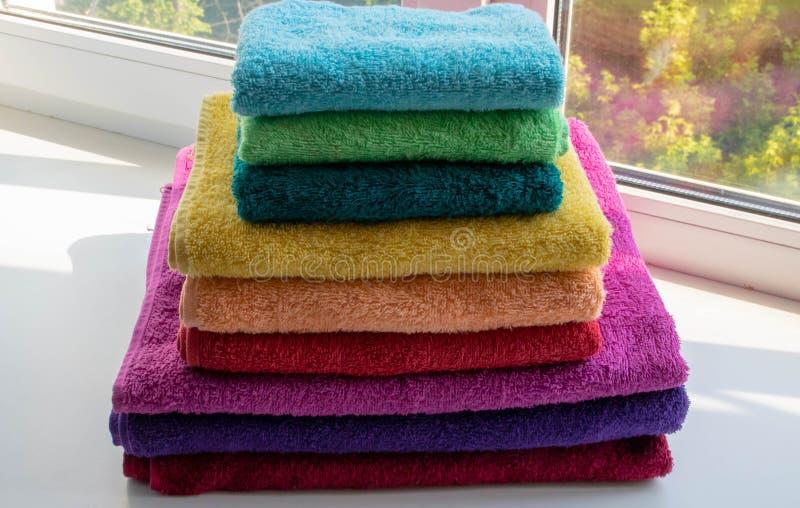 Mång--färgade dubbla handdukar i en bunt på fönstret royaltyfri foto