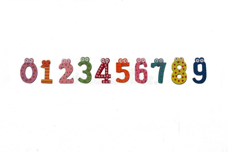 Mång--färgade nummer från noll till nio är på en vit bakgrund figures trä Roliga kulöra diagram royaltyfri foto