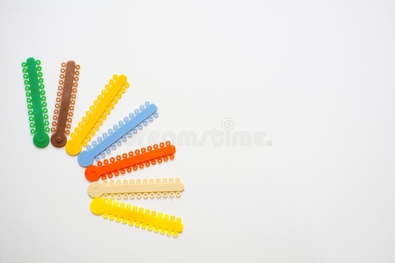 Mång--färgade orthodontic ligatures för justeringen av orthodontist'sens tänder på en ljus bakgrund royaltyfri fotografi