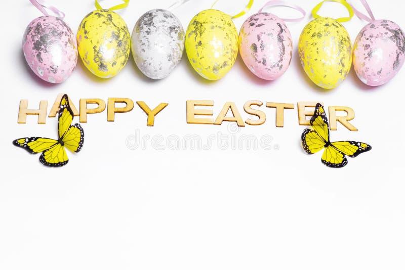 Mång--färgade påskägg på en vit bakgrund med en grupp av lycklig påsk för träbokstäver lyckliga easter arkivfoton