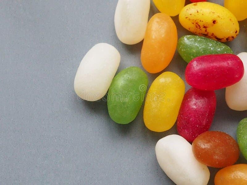 Mång- färgade sötsaker för geléböna på grå bakgrund arkivfoton