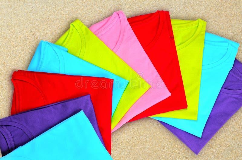 Mång--färgade t-skjortor för kvinna` s ligger på beige bakgrund fotografering för bildbyråer
