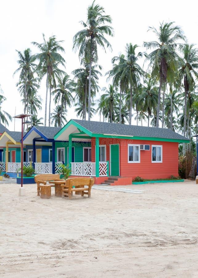 Mång--färgade trähus på stranden med gömma i handflatan och vit sand arkivfoto