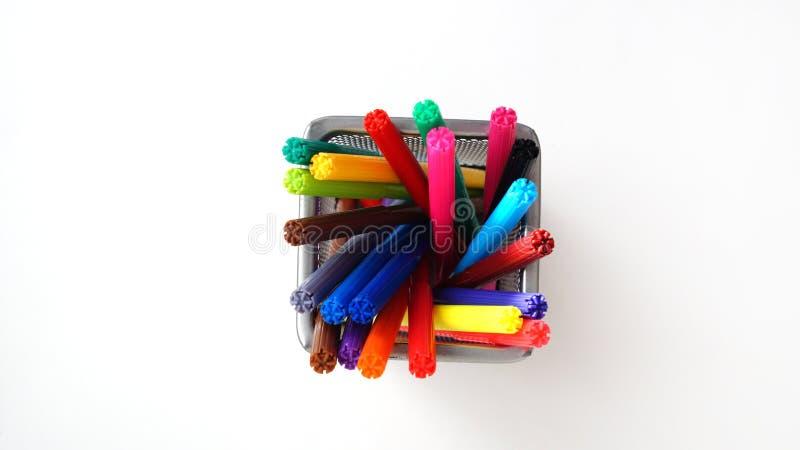 Mång--färgade tuschpennor står i ett genomskinligt exponeringsglas för ingrepp arkivbild