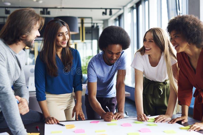 Mång- folkgrupp av affärsfolk som delar nya idéer arkivfoto
