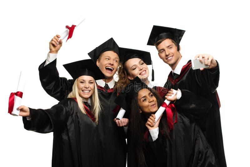 Mång- folkgrupp av graderade studenter arkivbild