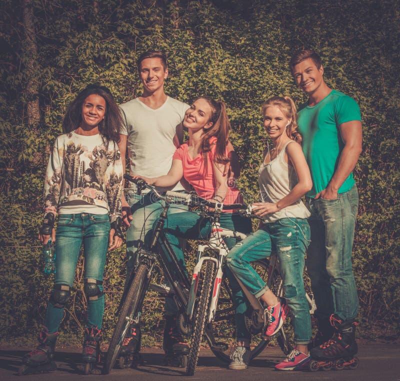Mång- folkgrupp av sportigt tonårs- i en parkera arkivbilder