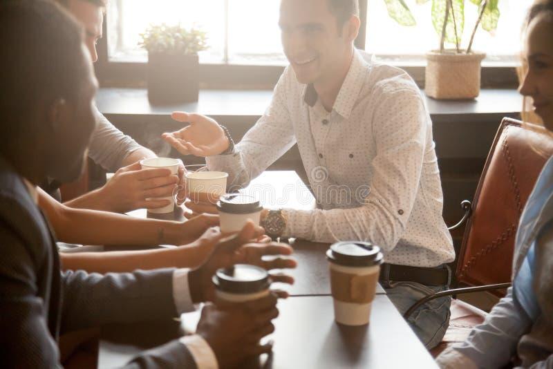 Mång- folkgrupp av vänner som tillsammans dricker kaffe i kafé arkivbilder