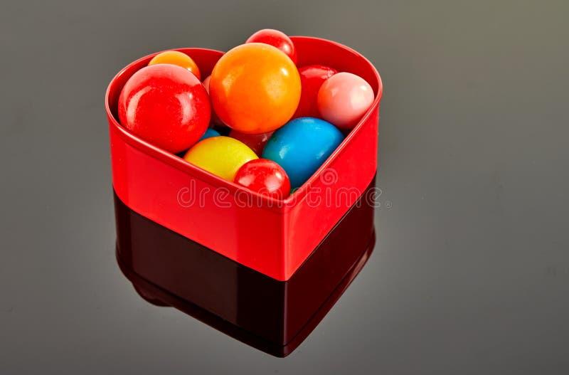 Mång- kulöra bollar av tuggummi på en grå bakgrund i en röd hjärta med reflexion royaltyfria foton