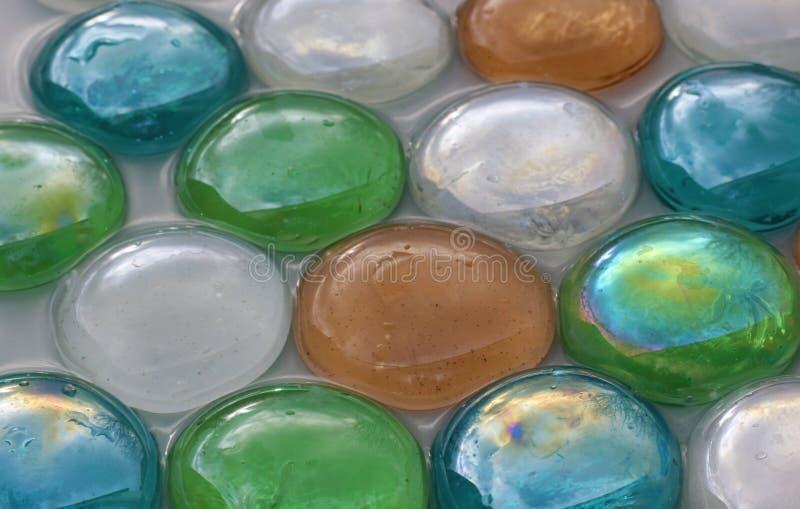 Mång- kulöra exponeringsglasstenar som ligger i vatten royaltyfri bild