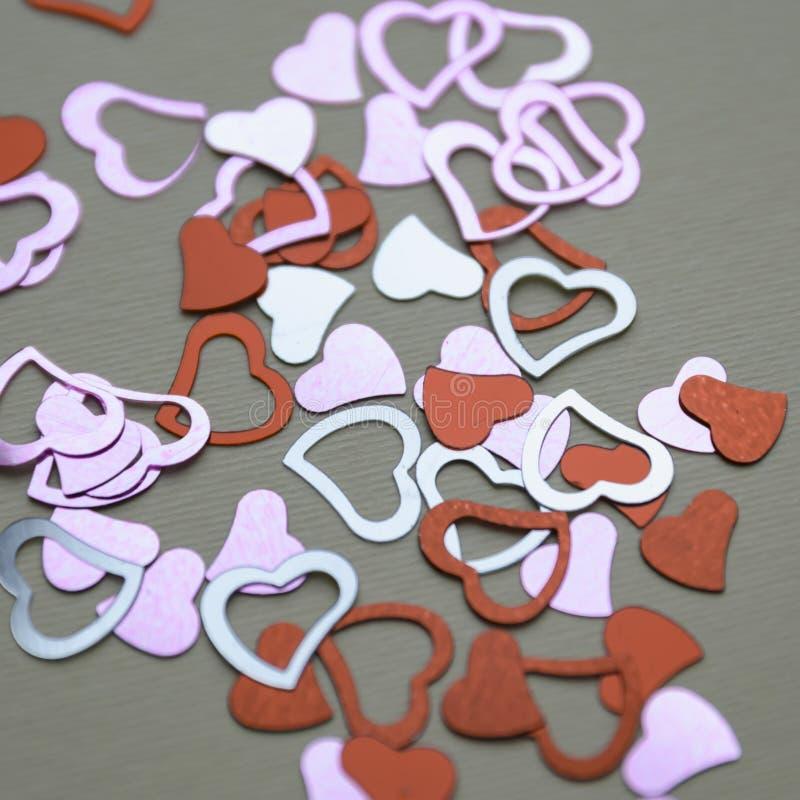 Mång- kulöra paljetter i formen av en hjärta på en beige bakgrund royaltyfri fotografi