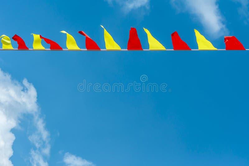 Mång- kulöra triangulära flaggor framkallar på bakgrunden av blå himmel Färgrika nöjesplatsflaggor arkivfoto
