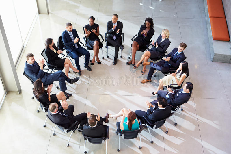 Mång--kulturell kontorspersonal som applåderar under möte royaltyfri fotografi
