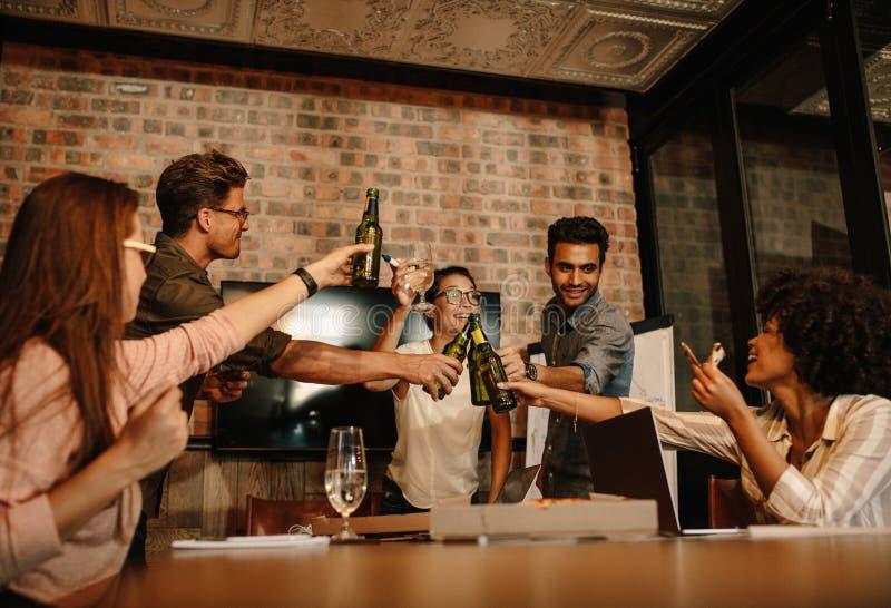 Mång--person som tillhör en etnisk minoritet affärsfolk som firar en framgång med öl royaltyfria bilder