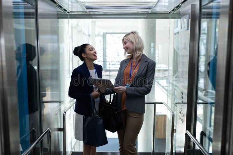 Mång--person som tillhör en etnisk minoritet affärskvinnor som i regeringsställning diskuterar över den digitala hissen för minne royaltyfria foton
