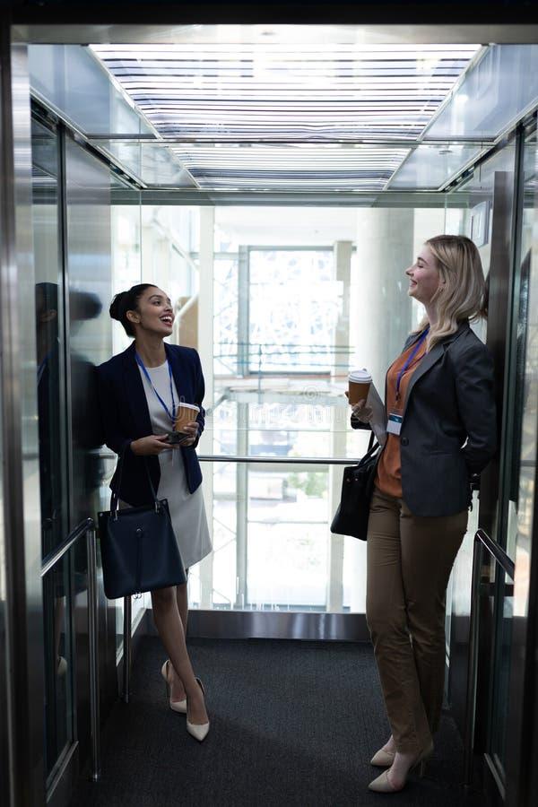 Mång--person som tillhör en etnisk minoritet affärskvinnor med kaffekoppen som i regeringsställning påverkar varandra med de hiss royaltyfria bilder