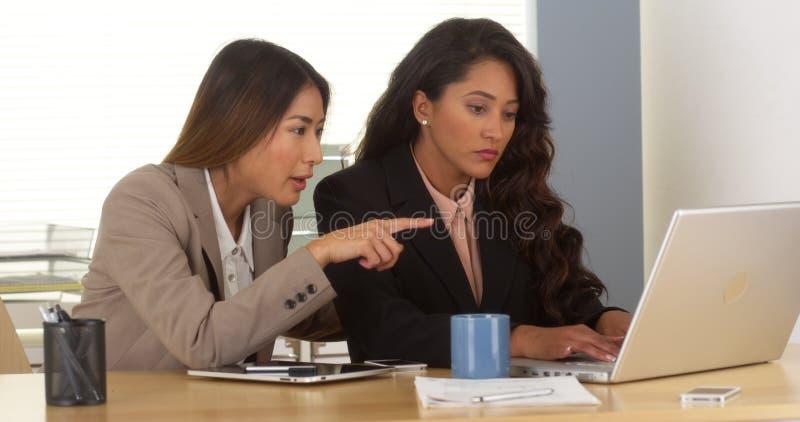 Mång--person som tillhör en etnisk minoritet affärskvinnor som arbetar på bärbara datorn arkivbilder