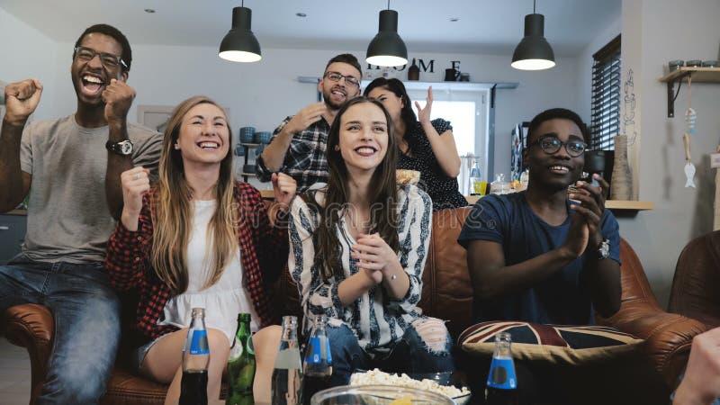 Mång--person som tillhör en etnisk minoritet fans går galna fira mål på TV Passionerade fotbollsupportrar skriker med armar lyftt fotografering för bildbyråer