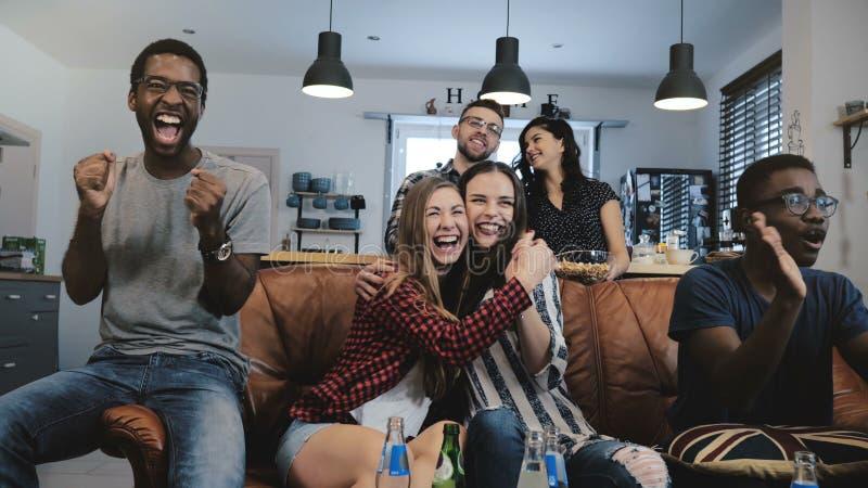 Mång--person som tillhör en etnisk minoritet fans går galna fira mål på TV Passionerade fotbollsupportrar skriker med armar lyftt royaltyfri bild
