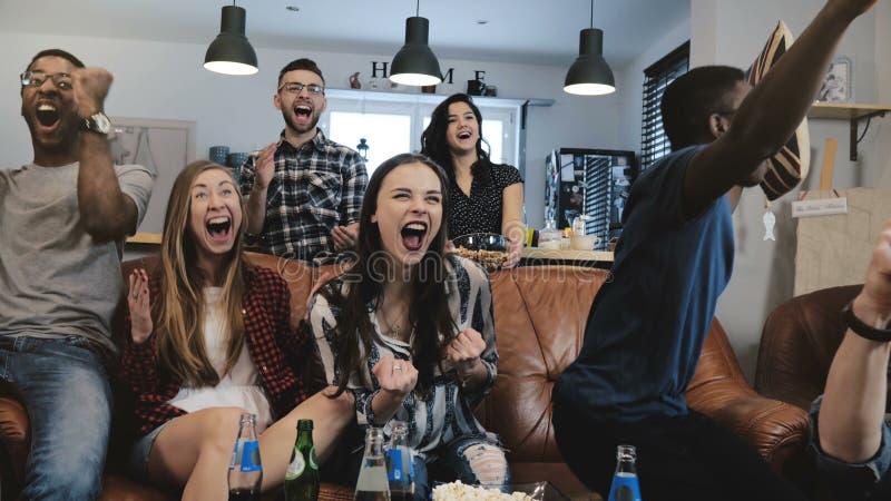 Mång--person som tillhör en etnisk minoritet fans går galna fira mål på TV Passionerade fotbollsupportrar skriker med armar lyftt arkivfoton