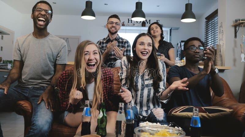 Mång--person som tillhör en etnisk minoritet fans går galna fira mål på TV Passionerade fotbollsupportrar skriker med armar lyftt royaltyfri fotografi