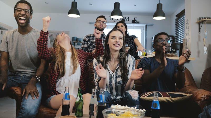 Mång--person som tillhör en etnisk minoritet fans går galna fira mål på TV Passionerade fotbollsupportrar skriker med armar lyftt arkivbilder